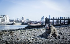 On a wide shingle foreshore, St Paul's and the London skyline as a backdrop, Liz adds another figure to a group on the shingle.