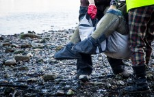 Liz's legs protrude from the carry sling, the shingle of the foreshore glistening wet beneath her.