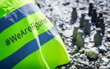 A high vis jacket with the project hashtag. In the background, 11 figures gather on the foreshore.