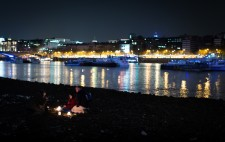 With a backdrop of city lights, two passersby sit on the foreshore facing Liz, in conversation, their faces illuminated by candlelight.