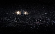 Seen from above, Liz sits with a few lanterns in front of her, almost camouflaged against the dark of the foreshore.