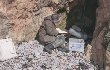 Facing into a hollow in the rocky cliff-face, Liz sits on beach stones, facing towards a large fluffy microphone on a stand and reading from an open folder.