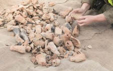 The figures, fired, burned and broken, are piled upon a hessian mat. Liz cups one of the figures in her hands.