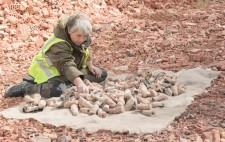Liz sits in an expanse of crushed bricks, in reds and pinks, against a backdrop of woodland. She sifts through the fired figures, which are piled on a hessian mat, their colours echoing those of the landscape.
