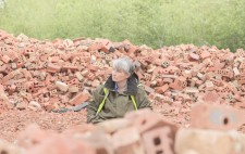 Surrounded by broken bricks, in reds and pinks, against a backdrop of woodland, Liz looks on pensively.