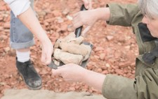 Liz hands over a small black shovel which holds several fired figures, their colour echoing the pinks of the crushed bricks on the ground below.