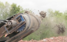 From the end of the milling machine, fragments of crushed figures are propelled into air.