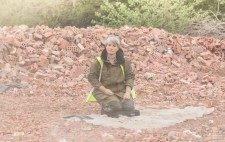 Liz sits, surrounded by bricks, watching the milling as dust drifts across.