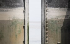 A gap opens between steel gates, the sea beyond. The image is horizontal strips of water and dry metal, sea and sky.