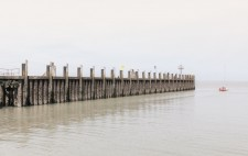 A wooden jetty, a stretch of vertical wooden planks, projects out to greys of water and sky, dwarfing a small sailing boat.