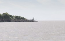 A rocky outcrop with a small lighthouse projects into open sea.