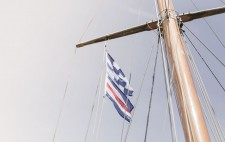 High up on a mast fly two flags: a blue and white checkered flag above one of horizontal stripes in blue, white and red.