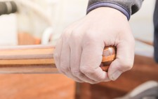 A hand rests on a wooden tiller.