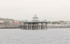 Rising from choppy water, with Clevedon seafront as a backdrop, is the wooden structure of the pier. The upper tier is surrounded by green railings with a pagoda at the centre.