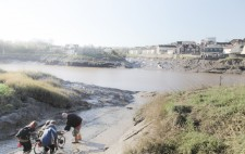 Liz is on a trike-wheelchair, tethered to a rope and assisted by three of the crew. The slipway opens out to wide banks of mud, the river beyond.