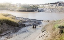 At the bottom of the slipway, with banks of mud giving way to the river beyond, Liz and a member of the production team sit on the ground, gazing out to the water.