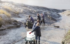 A wheeled cart with empty plastic crates is lowered down the slipway. Members of the team dig mud with spades from the riverbank.