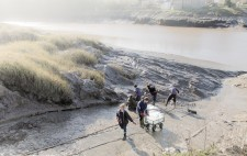 A wheeled cart with empty plastic crates sits at the bottom of the slipway. Members of the team dig mud with spades from the riverbank.