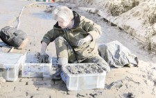 Liz sits on the slipway, filling crates with mud.