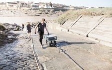 A wheeled cart with empty plastic crates is winched up the slipway. Below, members of the team dig mud with spades from the riverbank.