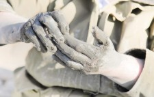 Liz's hands are coated in thick, wet mud, camouflaged against her coat.