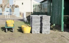 20 crates of mud, and some yellow tubs, are stacked, filled with mud.