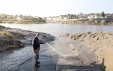 The slipway falls steeply down to the river at low tide, as a member of the sailing club hoses away the surface mud.