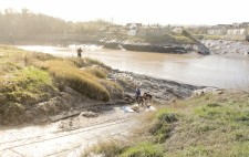 Members of the team dig the mud at the bottom of the slipway. On the grassy bank high above stands a camera operator at a tripod.