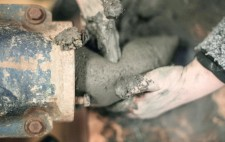 Hands receive the mud as it is extruded from the machine.