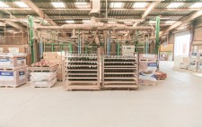 In the centre of a large manufacturing warehouse, metal shelf unit hold rows of clumped mud.